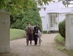 Hercule Poirot | Davenheim's House on Poirot, Driveway. Here is Chief Inspector Jaap from Scotland Yard with a bobbie, walking from a lovely house owned by a missing banker. Agatha Christie's Poirot, Hercule Poirot, Detective, Midsomer Murders, Miss Marple, Period Movies, Murder Mysteries, Seaside Towns, Filming Locations