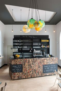 Destin Backstay Hostel Ghent 6 // Bar covered in old typesetting letters + globe light chandelier