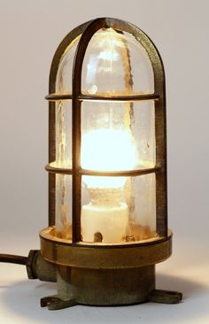 A vintage nautical ship lamp. Heavy brass casing and original pressed glass shade. It comes with its original ceramic bulb holder. The lamp has been