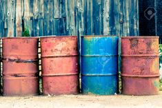 Photo presents four old used rust barrels for oil, petroleum, crude oil, mineral oil or petrol, three barrels are red and one is blue In background visible wooden storehouse, warehouse
