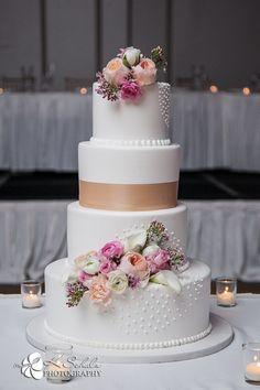 Winter wedding cake. Winter inspiration. Beautiful pink roses on wedding cake. Light brown ribbon on wedding cake