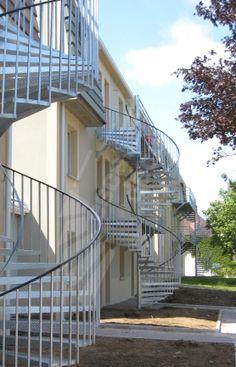 Photo S33 - Gamme Initiale - SPIR'DÉCO® Classique. Escaliers hélicoïdaux standards d'extérieur en acier galvanisé de style industriel pour accès terrasses. Marches en tôle larmée anti-dérapante pliée. © Photo : Escaliers Décors®
