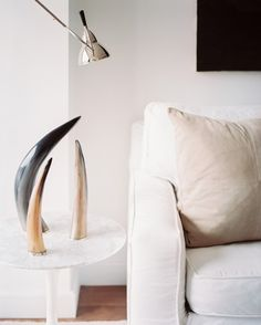 A trio of horns on a marble-topped tulip table.
