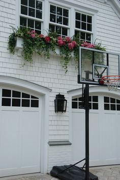 Shaker siding, pretty windows, arched top garage doors, large flower box