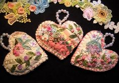 Using a vintage quilt from the 1940's, I cut out heart shaped designs and then embellished each one with Silk ribbon embroidery, dyed laces, charms, beads, sequins, and various tpes of threads. A loop large enough to act as a hanger was made us pearl beads.