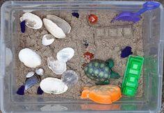 beach themed sensory bin:  moon sand  seashells  plastic sea creatures  shovels and sand molders