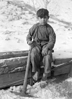"""Photographer Lewis Hine's original caption: """"Scott's Run, West Virginia. Miner's child - This boy was digging coal from mine refuse on the road side. The picture was taken December 23, 1936 on a cold day; Scott's Run was buried in snow. The child was barefoot and seemed to be used to it. He was a quarter mile from his home. 1936 - 1937."""""""