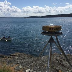 Pacific Northwest EarthScope Plate Boundary Observatory station maintentance, upgrading stations from GPS to GNSS antennas on April 29, 2015. Two researchers in a row boat taking sea water and marine life samples with netting in the background, with Frida
