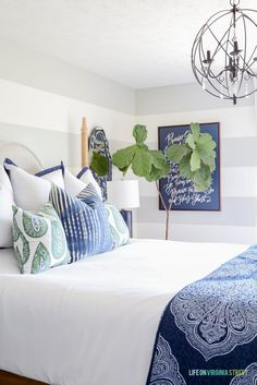 Bedroom with gray and white striped walls, white bedding, blue and green paisley pillows, navy blue linen lamps, iron orb chandelier and a navy blue Lindsay Letters Doxology canvas.