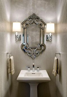 This jewel of a Powder Room was created by Design Connection, Inc. using a unique light reflective Silver Metallic Snakeskin Wallpaper.  A Crystal Ceiling Light Fixture & Crystal Sconces With Drum Shades accent this small but dramatic Powder Room.  Bathrooms By Design Connection, Inc. | Kansas City Interior Design http://designconnectioninc.com/portfolio #PowderRoom #BathroomRemodel #InteriorDesign
