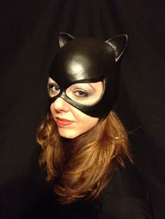 Meow, this Classic Catwoman Cowl is made of latex and comes in black, purple or classic purple/black combo