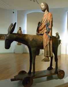 « le Palmesel (« Ane des Rameaux) : statue du Christ sur l'âne entrant à Jérusalem, monté sur chariot. Vers 1380.  Le « Palmesel » est une représentation du Christ monté sur un âne, placé sur une plate-forme en bois munie de roulettes. La statue servait au Moyen-âge pour la procession des rameaux commémorant l'entrée triomphale du Christ à Jérusalem. Le plus ancien exemplaire conservé du Palmesel date de la fin du XIIè (Musée National Suisse de Zurich).
