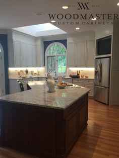 Custom kitchen remodel by Woodmaster Woodworks with stained island and white cabinets. Two toned kitchen cabinets.