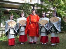 A man and several women dressed in heian robes.