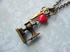 Colar com mini pingente de máquina de costura, tesoura e murano no formato de coração vermelho. R$30,00