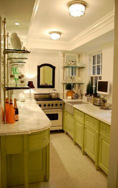 This Manhattan apartment galley kitchen by Greeson & Fast, has the sense of a French bistro, with the statuary marble counter tops, painted cabinets with bin pulls, and mirrored walls with brass and glass retail shelving.