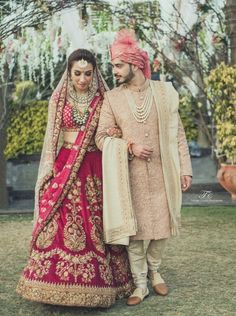 raspberry pink lehenga , pomegranate lehenga , deep ruby pink lehenga , deep pink lehenga , off white dupattta , double dupatta , coordinated bride and groom outfits , pastel pink sherwani , coral turbans , coral safa , long necklace , contrast jewellery