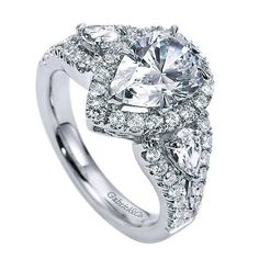 14K White Gold Pear Shaped 3-Stone Halo Diamond Engagement Ring. This ring features 1.20cttw of round pave set diamonds with two large pear shaped side diamonds. Features a subtle split shank of pave