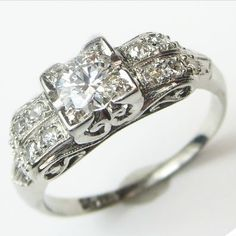 Best of Both: A bright center diamond is flanked by sleek doubled rows of accent diamonds with curling vine detail is tucked underneath. Ca.1940. Maloys.com