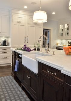 White cabinets, dark stained center island with light counters (honed carerra marble), paper towel holder. (walls are Benjamin Moore Marilyn's Dress 2125-60 Paint)
