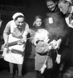 October 1945: A child crying as she is sprayed with DDT delousing powder at Nicholsburger Platz School, Wilemsdorf, Germany