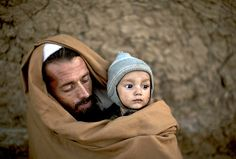 Pakistani Ibrahim Mohammed, 42, who was displaced with his family from Pakistan's tribal region of Mohmand Agency due to fighting between the Taliban and the army, wraps himself and his son Mashal, 1, with a shawl to avoid the evening cold, while sitting in front of his home in a poor neighbourhood on the outskirts of Islamabad, Pakistan on November 15, 2013. (Muhammed Muheisen/AP)