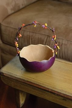 """Retired -This baskets is great for sharing your Easter candy, eggs or carrots. The handle is decorated with spring colored berries and the basket has a scalloped edge. This basket is purple in color and approximately 5"""" in diameter."""