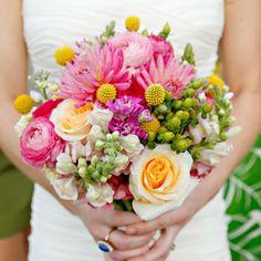 bright arrangement showcasing dahlias, roses, craspedia and berries