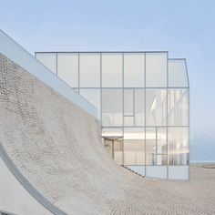 Steven Holl Architects have collaborated with Brazilian architect Solange Fabião on this wave-shaped museum of the sea in Biarritz, France, which opened this week. The Cité de l'Océan et du Surf has a cobbled plaza over the concave roof, which gently descends to meet the sloping ground. The galleries of the museum are contained within this curving concrete block, while two acid-etched glass boxes