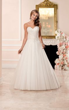 This satin A-line wedding dress by Stella York has a princess cut strapless sweetheart bodice with clear beading on lace that catches the light. The tulle skirt fans full into a sweep train. Choose from a corset closure or a zipper closure under fabric-covered buttons.