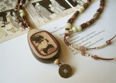 Mixed media pendant. Water slide transfer on Tagua nut, with bead frame. By Peppina Pöyhönen.