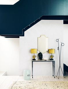 Thin console table with matching yellow table lamps, garden stool, and teal geometric space above