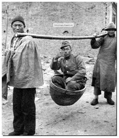 A Japanese army officer makes two Chinese men carry him