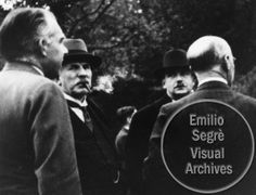 Left to right: Niels Bohr, Ernest Rutherford, and R. H. Fowler outside at the Copenhagen Conference at the Niels Bohr Institute. Caption on photograph reads 'Carlsberg Park.' This photograph was originally part of an album owned by Victor Weisskopf, however, the image number is not known, but assumed to be 35 or 36. Credit line:  Photograph by Paul Ehrenfest, Jr., courtesy AIP Emilio Segre Visual Archives, Weisskopf Collection.