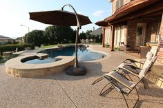 Beautiful exposed aggregate concrete pool deck. By: Outdoor Signature in Argyle, TX