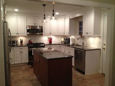 Slate Porcelain Tile in Versailles pattern, White cabinets with distressed edges, white subway tile, pottery barn pendants, wood island, black granite counters, stainless appliances