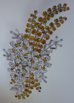 The Queen`s Australian Wattle Diamond brooch. This brooch was a gift from the people of Australia when the Queen made her 1st Royal Tour in 1954. The brooch depicts Australia`s national flower, the wattle & three native Australian tea tree blossoms. It contains about 150 diamonds, some in quite rare colours of yellow for the wattle flowers, some very light blue for the leaves & some white diamonds in the tea tree flowers.