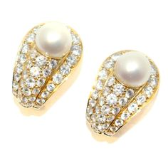 A very pretty pair of Cartier pearl and diamond clip earrings in their original box. Each earring contains approximately 2.50 carats of brilliant cut diamonds with a white cultured pearl in the centre. Circa 1980s