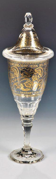 Bruno Mauder (Entwurf, zugeschr.), Glasfachschule Zwiesel, um 1921 Deckelpokal mit Widmung  Farbloses Glas mit Schliff und Goldbemalung. Mit Widmungsaufschrift in Gold: ''DEM EIFRIGEN FÖRDERER DES B. FACHSCHULWESENS SR. EXZ. REG. PRÄSIDENT DR. RITTER VON BLAUL - GEWIDMET VOM VERBAND BAYERISCHER FACHSCHULMÄNNER IN MÜNCHEN 1921''. Bodenunterseite bez.: FZ (in Gold aufgemalt). H. 33,5 cm Fountain, Ceramics, Glass, Gold, Mockup, Knight, Ceramica, Pottery, Drinkware