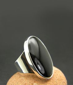 Large black onyx ring, sterling silver, huge oval black stone, statement ring, cocktail ring, boho black jewelry, Black stone ring Statement sterling silver with ring huge oval black onyx stone Big oval black onyx cabochon stone beautifully polished set in sterling silver bezel on wide band The stone is 30 mm * 20 mm .The shank of the ring starts from 18 mm and ends to 7 mm at the back The ring in the photos is US size 7,UK O . If you need another size select from the variation or leave a…