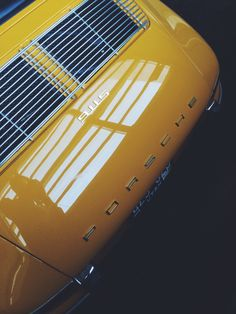 Angled shot of a vintage yellow Porsche 911.