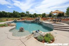 This swimming pool has a natural rock water feature, deck jets and raised deck with a lounge.