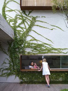 From the garden deck, Sophia Cóser talks to sister Helena and mother Piti through a wide, low-slung window typical of architect Marcio Kogan. Photo by: Crisobal Palma | Read more: http://www.dwell.com/articles/Sao-Paulo-Brazil-dwelling.html