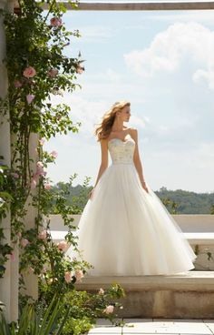Mori Lee Voyage 67491 is breath taking! This gown features a fitted bodice, detailed in lace with hints of silver stoning. The sweetheart neckline is outlined in lace and the bodice features a corset back. The crinoline skirt features pleats at the waist line and is full length with a short train in the back.