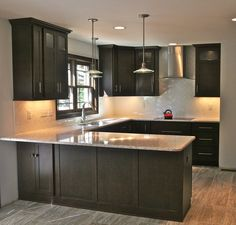 Modern kitchen with shaker cabinetry in a dark wood finish. Accented by light granite countertops, sleek pendant lights and a white subway tile backsplash in a herringbone pattern. #kitchencabinetry