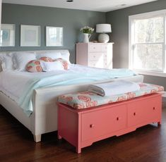 The bright pink of the end of bed storage chest brings a spring-like life and appeal to this feminine bedroom