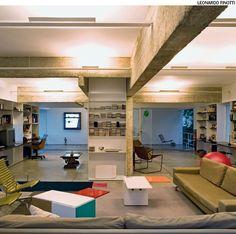 Em vez de rebaixar o teto com gesso para embutir a iluminação, o arquiteto Paulo Mendes da Rocha instalou luminárias metálicas horizontais com lâmpadas voltadas para o teto e fixação na metade da altura das vigas de concreto aparente.