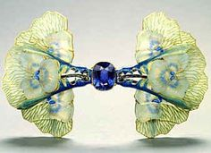Joyeria Art Nouveau de René Lalique. Three overlapping pansies on either side of a central, simulated step-cut sapphire combine molded glass blossoms with openwork enameled petals growing out of stems also covered with translucent blue enamel, c.1903
