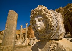 Roman head in the ruins of Leptis Magna, Libya. _  Leptis Magna, also known as Leptis Changes was a thriving city of the Roman Empire. Its ruins are located in Al Khums, Libya. It was one of the most beautiful cities of the Roman Empire due to Septimius Severus, who rose and embellished, rising stately public buildings, a port, a market, warehouses, shops and residential neighborhoods. The city was probably founded by Phoenician settlers in 1100 BC