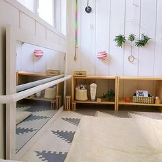 The pull up bar across the floor mirror is the classic Montessori nursery addition for a mobile baby.